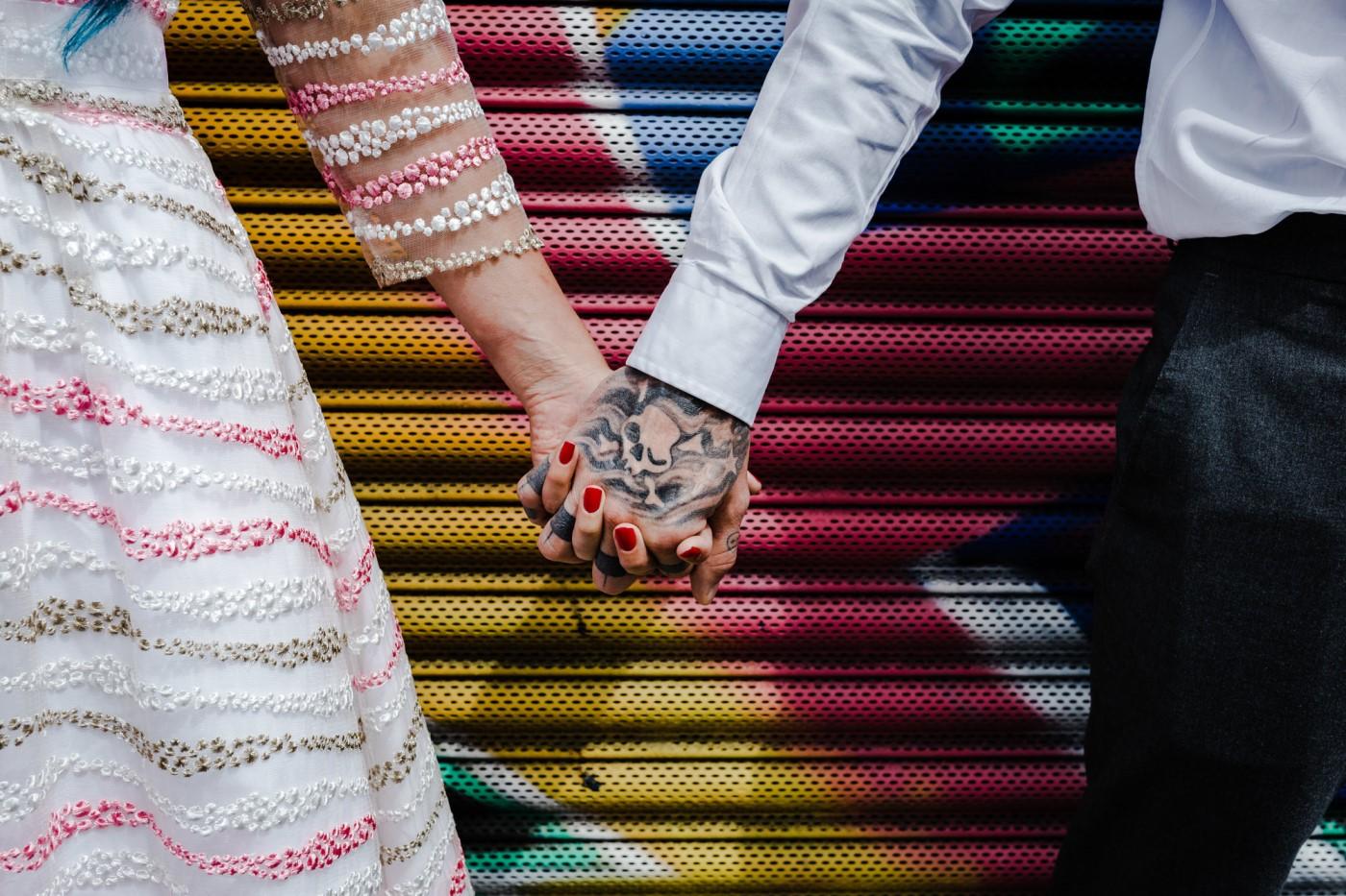 kirsty rockett photography - urban wedding against graffiti holding hands